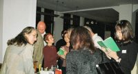 Menschen halten grüne Bücher aufgeschlagen in den Händen rund um einen Tisch voller Infomateialien, Quelle: DTF