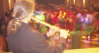 Mann spielt Flöte auf der Bühne vor tanzendem Publikum, Quelle: DTF