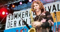 Musiker auf der Bühne vor Banner des Sommerfestes, Quelle: DTF
