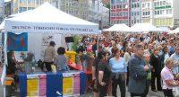 Menschen auf dem Marktplatz neben Zelt des DTF, Quelle: DTF
