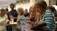 Menschen im Publikum lesen Flyer des Sommerfestivals, Quelle: DTF