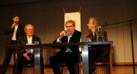 Diskussionsteilnehmer*innen sitzend an einem Holztisch auf dem Podium, Quelle: DTF