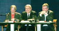 drei Männer sitzen an einem Holztisch auf dem Podium, Quelle: DTF