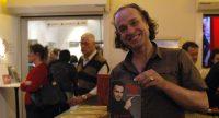 Mann hält lächelnd ein Buch von Fatih Cevikkollu, Quelle: DTF