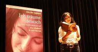 Nilgün Tasman liest aus ihrem Buch vor Banner mit dem Buchcover, Quelle: DTF