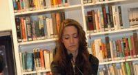junge Frau liest mit gekreuzten Beinen aus einem aufgeschlagenen Buch vor, Quelle: DTF