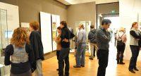 Menschen im Ausstellungsraum schauen sich ausgestellte Wände mit Text und Bilder an, Quelle: DTF