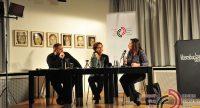 Diskussionsteilnehmer*innen am Holztisch vor Banner des DTF, Quelle: DTF