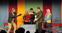 Schauspieler*innen auf der Bühne vor buntem Hintergrund vor Silhouette des Publikums, Quelle: DTF