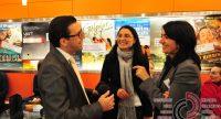 zwei Frauen und ein Mann im Gespräch miteinander vor Wand mit Kinopostern, Quelle: DTF