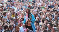Mann im blauen Mantel spielt Saiteninstrument mitten im Publikum, Quelle: DTF