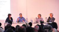 Diskussionsteilnehmer sitzend an weißen Tischen mit Mikrofonen und Wasserflaschen vor sich vor Silhouette des Publikums, Quelle: DTF