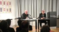 zwei Männer sitzend am Tisch neben Rednerpult vor Silhouette des Publikum, Quelle: DTF
