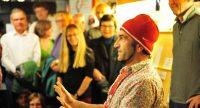 Mann mit roter Mütze sitzt mit erhobeenen Händen vorm Publikum, Quelle: DTF