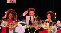 ein Mann und zwei Frauen sitzend am dicht bedeckten roten Tisch mit Länderflaggen, Quelle: DTF