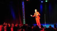 Mann im roten Anzug spricht gestikulierend auf der Bühne vor Silhouette des Publikums, Quelle: DTF