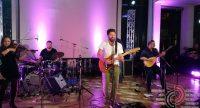 vierköpfige Band spielt Musikinstrumente im lila beleuchteten Saal, Quelle: DTF