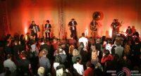 Band auf rot beleuchteter Bühne vor tanzenden Menschen, Quelle: DTF