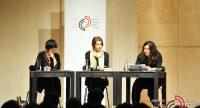 drei Frauen sitzend an Holztischen vor Banner des DTF vor Silhouette des Publikums, Quelle: DTF