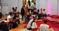 Kinder und Erwachsene sitzend und stehend in einem Saal mit roten Sitzkissen, Quelle: DTF