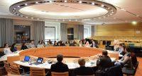 Menschen sitzen rund um einen großen, runden Holztisch, Quelle: DTF