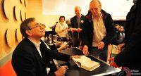 Mann an einem schwarzen Tisch mit aufgeschlagenem Buch schaut zu vor ihm laufenden Männern, Quelle: DTF