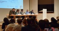 Diskussionteilnehmer sitzend am langen Tisch unter Projektion einer Karte, unter ihnen das Publikum, Quelle: DTF