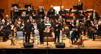 Orchester auf dem Podium mit vier Männern in schwarzen Hemden ganz vorne, Quelle: DTF