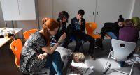 junge Menschen sitzen auf Plastikstühlen, eine junge Frau beugt sich auf den Boden runter, um auf einem Plakat zu schreiben, Quelle: DTF