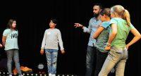 Kinder auf der Bühne , Mann im blauen Hemd steht im Bildhintergrund, Quelle: DTF