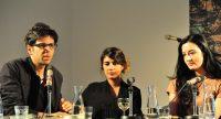 zwei Frauen und ein Mann sitzend an einem Holztisch, Quelle: DTF