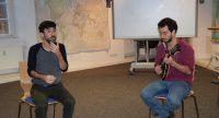 zwei sitzende Männer, der eine spielt Gitarre, Quelle: DTF