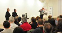 Mann im grauen Pullover spricht gestikulierend ins Mikrofon an einem Rednerpult in Richtung zweier sitzender Herren vor Köpfen des Publikums, Quelle: DTF