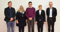 drei Männer und zwei Frauen stehen lächelnd vor einer weißen Wand, Quelle: DTF