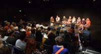 Frauen im Kostüm auf der Bühne sitzend auf Stühlen vor Publikum, Quelle: DTF