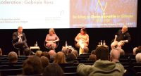 Diskussionteilnehmer sitzend auf einem Podium vor Leinwand vor mittelmäßig besetzten Stühlen im Publikum, Quelle: DTF