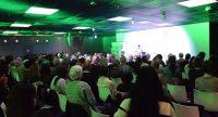 Saal voller Menschen auf weißen Stühlen vor der stark grün beleuchteten Bühne, Quelle: DTF