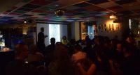 voll besetzter Saal mit bunter Decke und zwei Menschen die neben einer weiß leuchtenden Leinwand stehen, Quelle: DTF