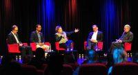 Diskussionsteilnehmer sitzend auf roten STühlen vor Silhouette des Publikums, Quelle: DTF