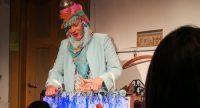 Frau im türkisen Mantel mit Kopftuch steht am Puppentheater, Quelle: DTF