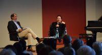 Musiker und Gesprächspartner sitzend und lachend auf dem Podium vor beige-rotem Hintergrund, Quelle: DTF