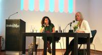 Dilek Güngör und Moderatorin sitzen an einem Holztisch neben Rednerpult des Literaturhauses, Quelle: DTF