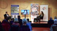 Frauen auf dem Podium mit Bildschirm der Live-Übertragung eines Mannes, Quelle: DTF