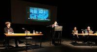 Autor*innen auf dem Podium, Abdul Vahap liest stehend am Rednerpult, Quelle: DTF