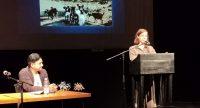 Autor*innen auf dem Podium, Maria liest stehend am Rednerpult, Quelle: DTF