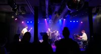 Musiker auf der Bühne vor Silhouette des Publikums, Quelle: DTF