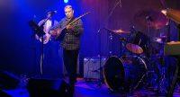 Bassist, Saz-Spieler und Schlagzeuger auf hell beleuchteter Bühne, Quelle: DTF