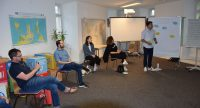 Workshopteilnehmer*innen sitzen in einem Halbkreis und hören einem Moderatoren zu, Quelle: DTF