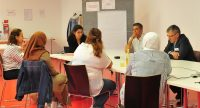 Sieben Männer und Frauen sitzen um einen Workshop-Tisch im Gespräch., Quelle: DTF