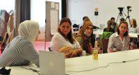 Vier Frauen mit und ohne Kopftuch sitzen nebeneinander an einem Tisch auf dem ein Laptop steht., Quelle: DTF